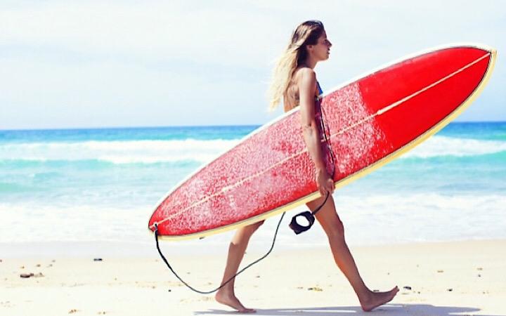サーフボードを持ちながら歩いているサーファー