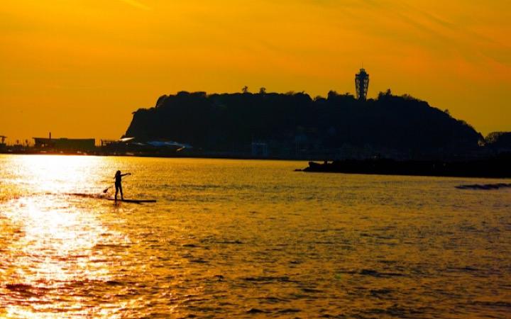 夕暮れ時の海でサーフィンをしているサーファー