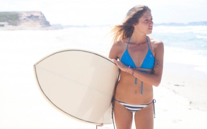 サーフボードを持ち海を見ているサーファー