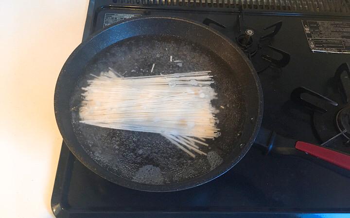 半分に折った稲庭うどんをフライパンで茹でている写真