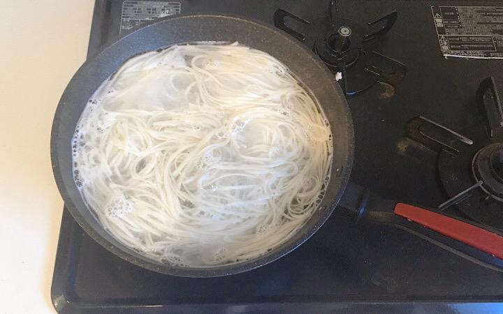 フライパンで稲庭うどんを茹でている写真