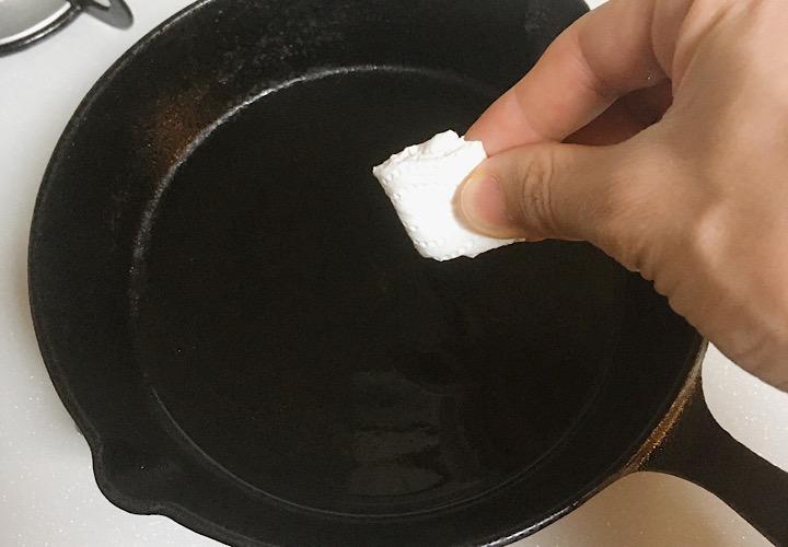 キッチンペーパーでオイルをスキレットに馴染ませている写真