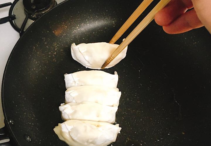 菜箸を使って餃子を並べている写真