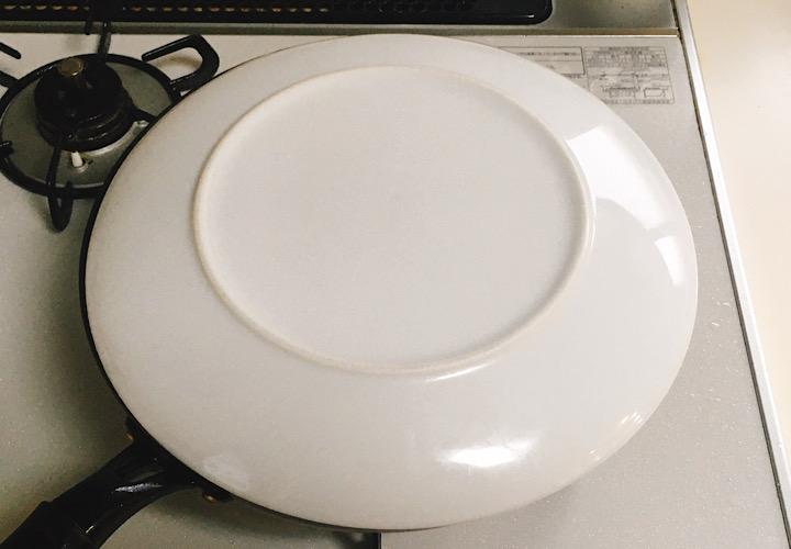 大きな平皿をフライパンにかぶせている写真