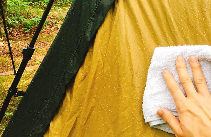 テントの露をタオルで拭き取っている様子